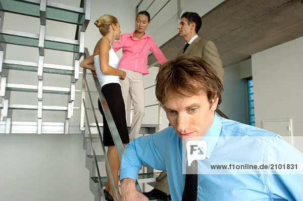 Businessman standing by staircase with colleagues in background