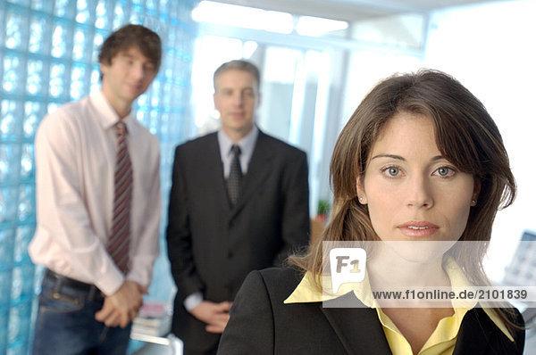 Kauffrau im Büro mit Kollegen im Hintergrund