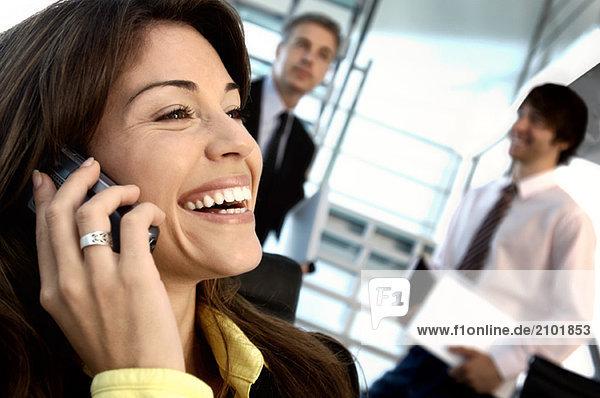 Geschäftsfrau mit Handy und Kollegen im Hintergrund