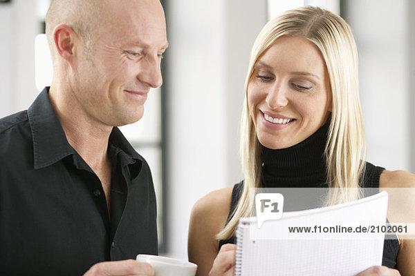 Zwei lächelnde Geschäftsleute lesen ein Dokument  fully_released