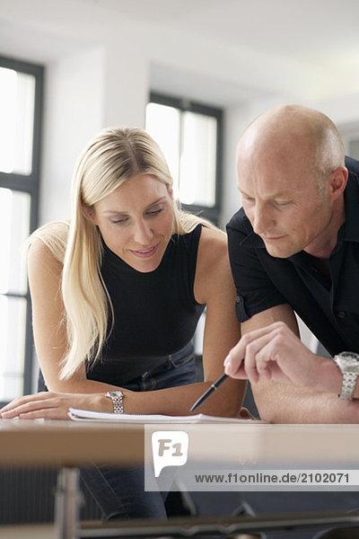Zwei Geschäftsleute lehnen an einem Tisch und studieren Unterlagen  fully_released