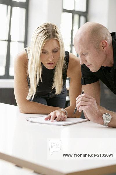 Zwei Geschäftsleute stehen gebeugt über einem Tisch und lesen ein Dokument  fully_released