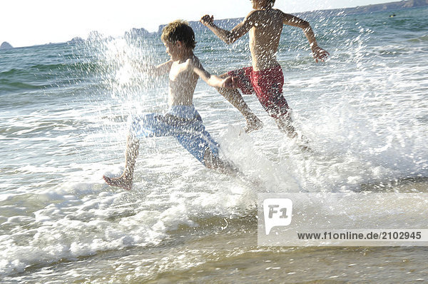 Side profile of two brothers running in water on beach