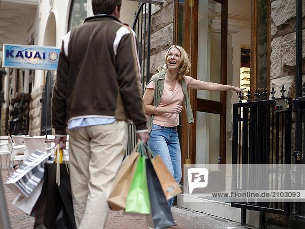 Frau blickt auf Mann tragen Tragetaschen