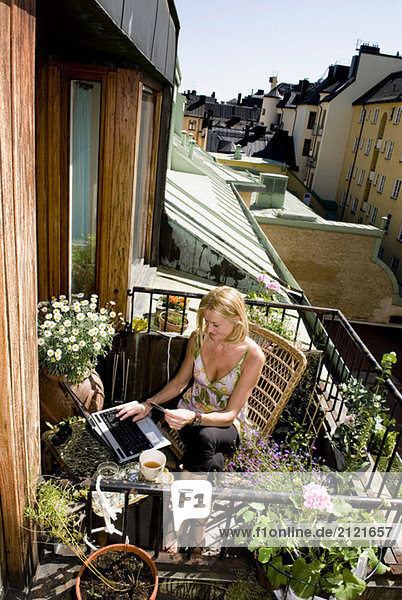 Frau auf dem Balkon sitzend