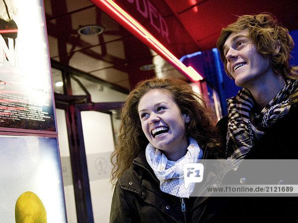 Kerl und Mädchen außerhalb des Kinos
