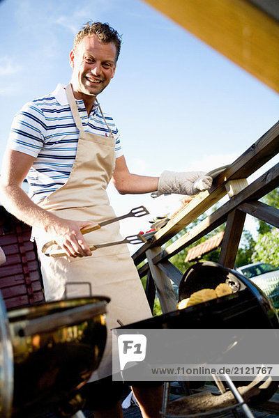 Man in an apron barbecuing