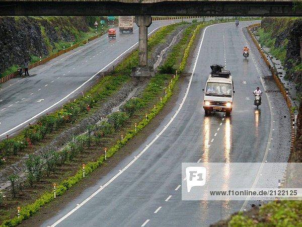 Vehicles are traveling on a national  Pune_ Banglore highway in rainy season. Pune  Maharashtra  India.