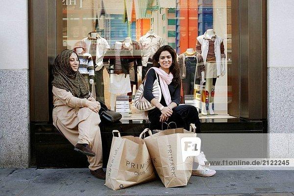 Zwei schöne und junge Muslime Damen vor das Fenster eines Kaufhauses sitzen  eine Pause von einer langen shopping-Tour und haben ihre Einkaufstüten davor  Oxford Street  London  Großbritannien  Europa
