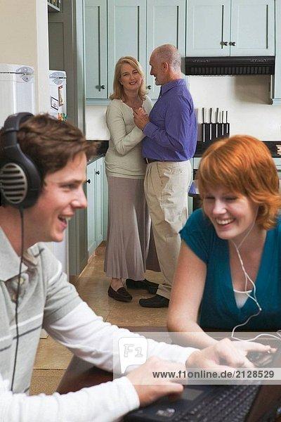 50_60 Jahre paar Tanz zu Musik von Stereo/Radio in Küche mit Teen/Erwachsene Kinder sitzen im Speisesaal Musikhören auf Laptop & Ipod.