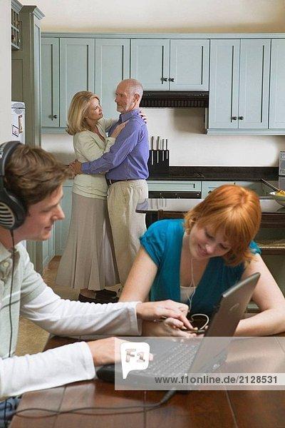 50-60 Jahre paar Tanz zu Musik von Stereo/Radio in Küche mit Teen/Erwachsene Kinder sitzen im Speisesaal Musikhören auf Laptop & Ipod.