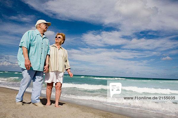 älteres Paar einher Strand entlang Schlendern