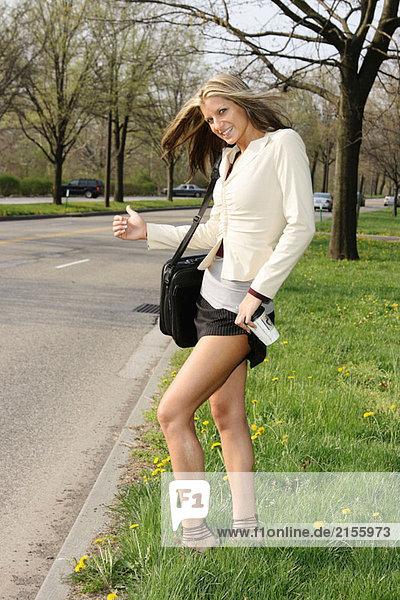 Junge Frau im Business Attire Daumen für eine Fahrt zu arbeiten