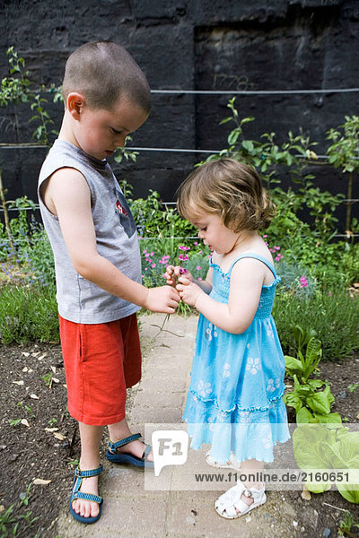 Brother and sister in garden.