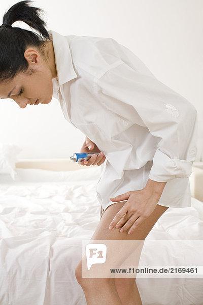 Frau Apllying Salbe auf Bein
