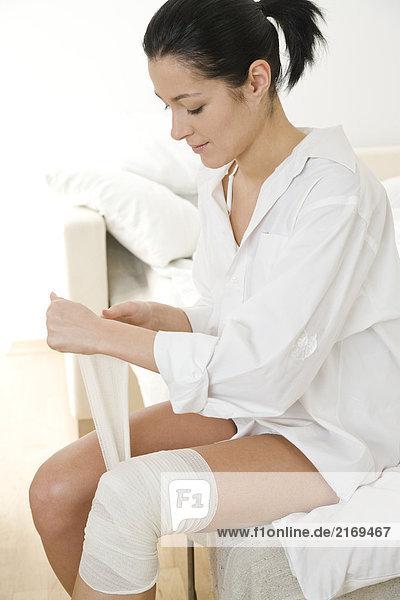 Frau setzen Verband auf ihrem Knie