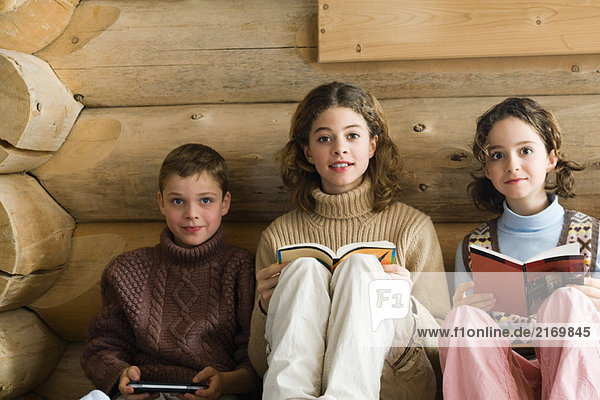 Three young siblings sitting side by side  reading and playing video game