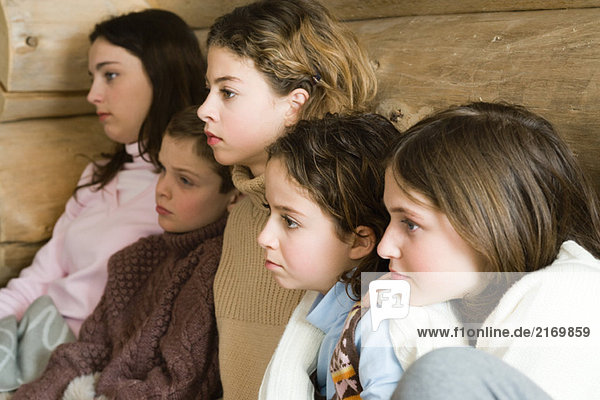 Group of teens and preteens watching TV together  side view