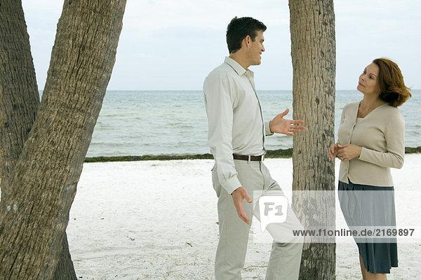 Mann und Frau stehen neben einem Baumstamm am Strand und lächeln sich an.