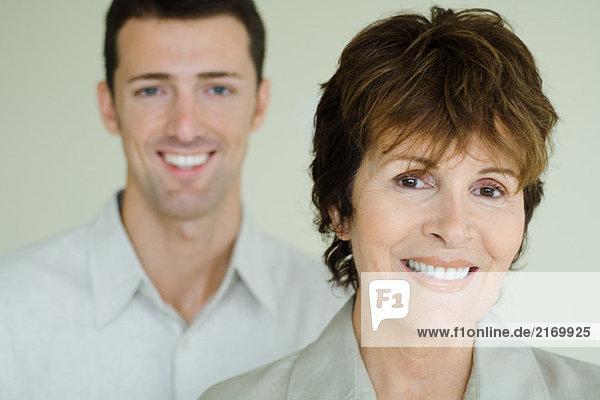 Seniorin vor erwachsenem Sohn  beide lächelnd vor der Kamera  Fokus auf den Vordergrund