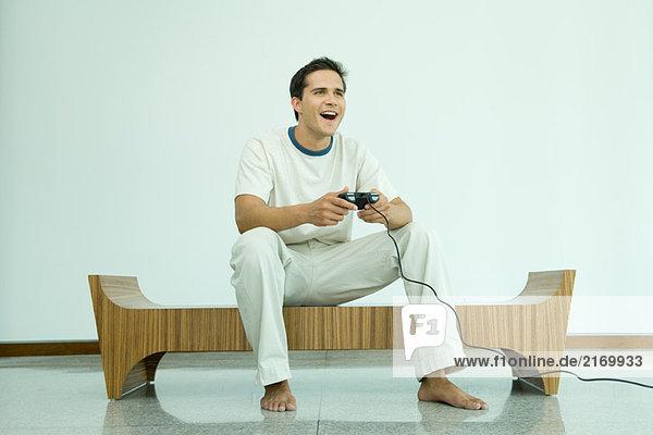 Junger Mann spielt Videospiel  lächelnd