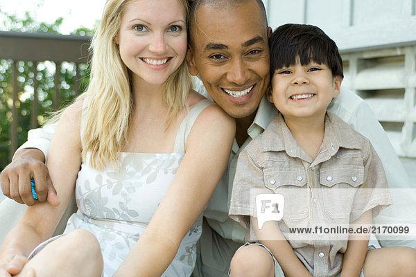 Familie lächelt gemeinsam vor der Kamera  Porträt