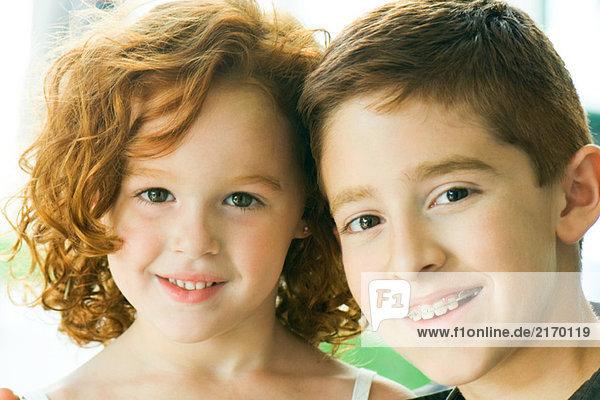 Bruder und Schwester lächeln gemeinsam in die Kamera  Porträt
