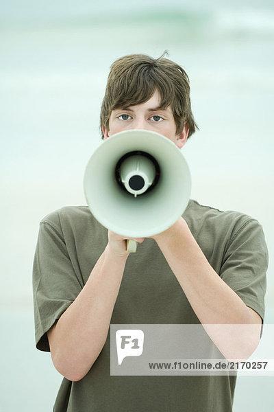 Teen boy using megaphone  front view
