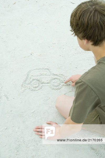 Teen boy drawing car in sand