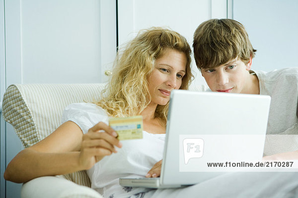 Woman and teenage son making credit card purchase online