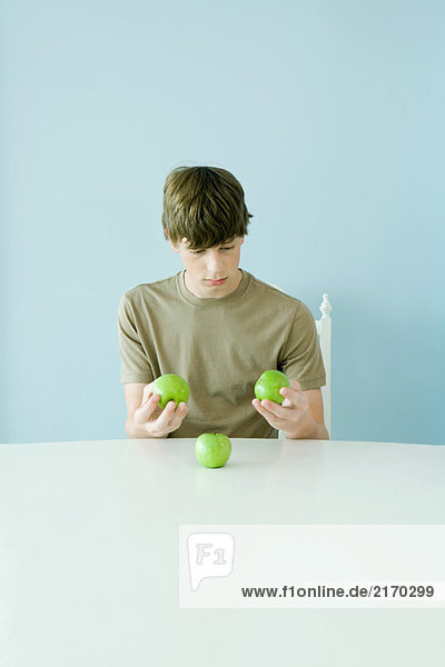 Teen boy holding up comparing three apples