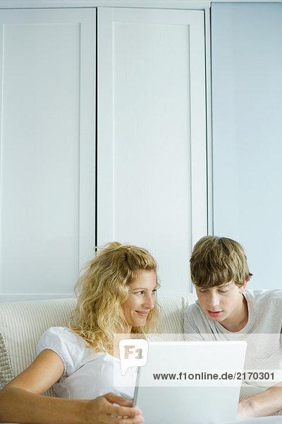 Frau und Teenager-Sohn mit Laptop zusammen