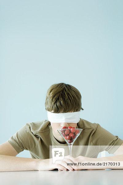 Teen boy wearing blindfold  smelling glass full of cherries