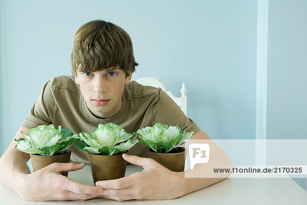 Teen boy protecting potted plants  looking at camera