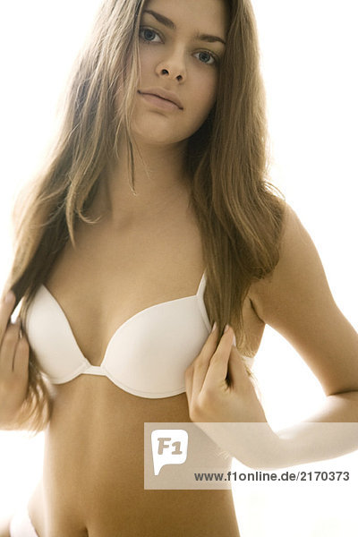 Young woman in bra holding ends of hair with both hands  looking at camera