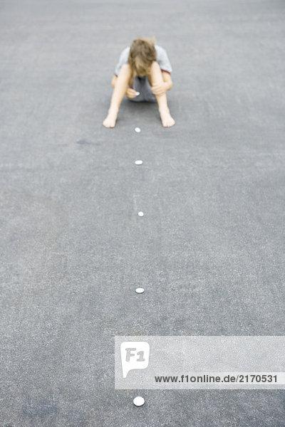 Junge sitzt auf dem Boden und arrangiert eine Reihe von Kieselsteinen.