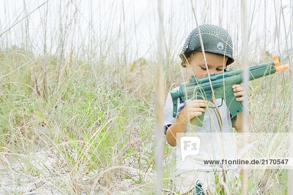 Kleiner Junge spielt mit einer Spielzeugpistole  trägt einen Helm und schaut nach unten.