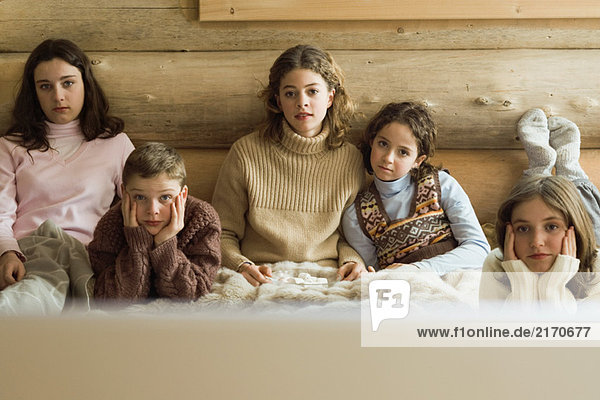 Group of teen and preteen friends and siblings watching TV  front view