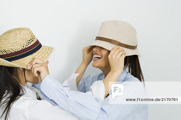 Zwei junge Freunde  die sich gegenseitig Hüte über die Gesichter ziehen.