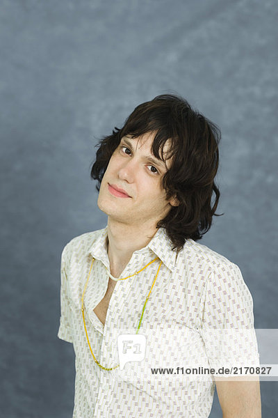 Teenage boy looking at camera  head tilted  portrait