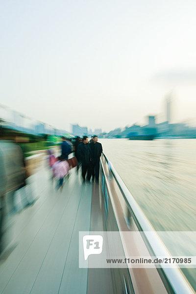 Fußgänger  die am Flussufer entlang gehen  verschwommene Bewegungen