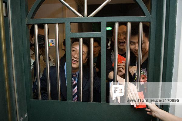Chinesische Hochzeitstür Tradition  Männer schauen durch Gittertür  halten Geschenkumschläge  lachend und lächelnd