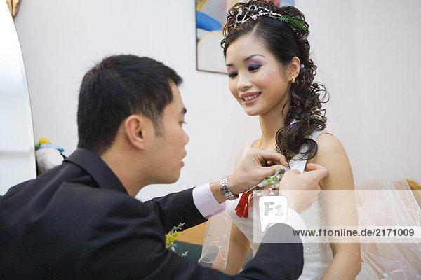 Bräutigam  der Corsage auf das Brautkleid klebt.