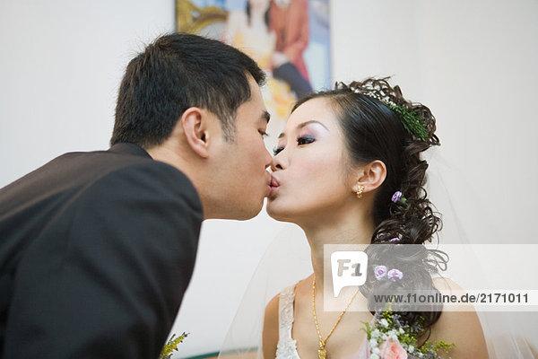 Braut und Bräutigam küssen  Seitenansicht