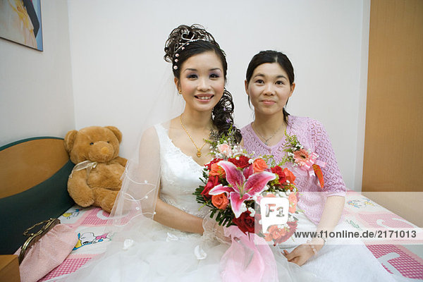 Braut sitzt auf dem Bett neben der Brautjungfer  lächelt in die Kamera.