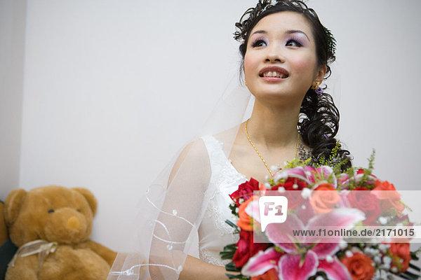 Braut hält Blumenstrauß  lächelnd  Teddybär im Hintergrund
