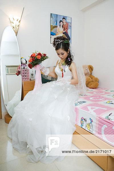 Braut auf dem Bett sitzend  mit Blick auf das Kleid  volle Länge