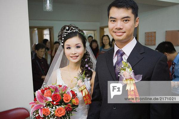 Braut und Bräutigam in Korsagen  lächelnd vor der Kamera  Freunde und Familie im Hintergrund