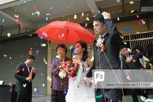 Chinesische Hochzeit  Braut und Bräutigam verlassen unter Konfetti  Braut mit rotem Sonnenschirm bedeckt