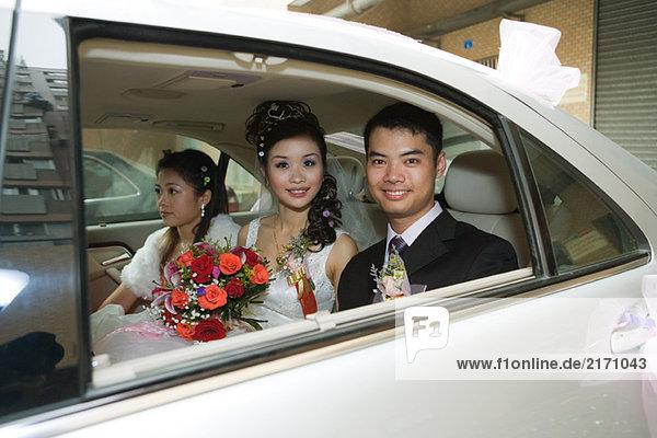Braut und Bräutigam im Auto mit Brautjungfer  lächelnd vor der Kamera